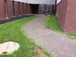 L'environnement de la porte 9 avant les travaux. Une allée de poussière de roche bordée de gazon.